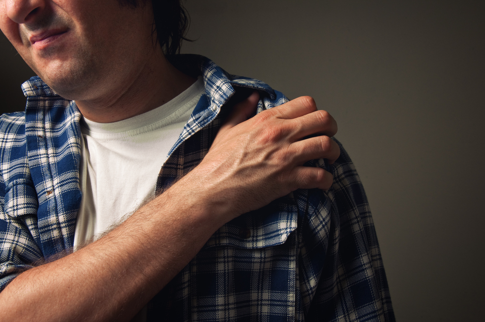Man holding his painful shoulder