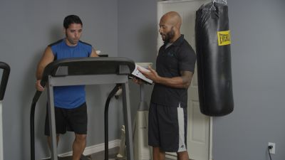 personal trainer talking to client on a treadmill