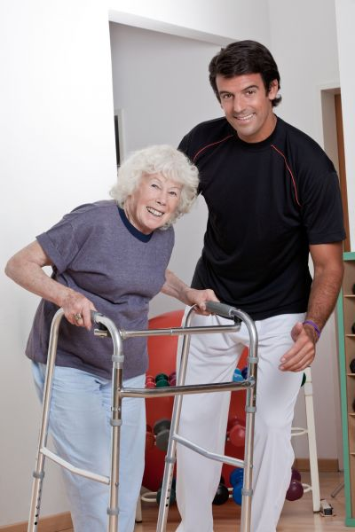 Therepaist helping patient with a walker