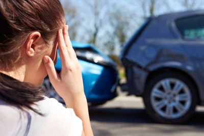 Stressed woman looking at her rear ended vehicle