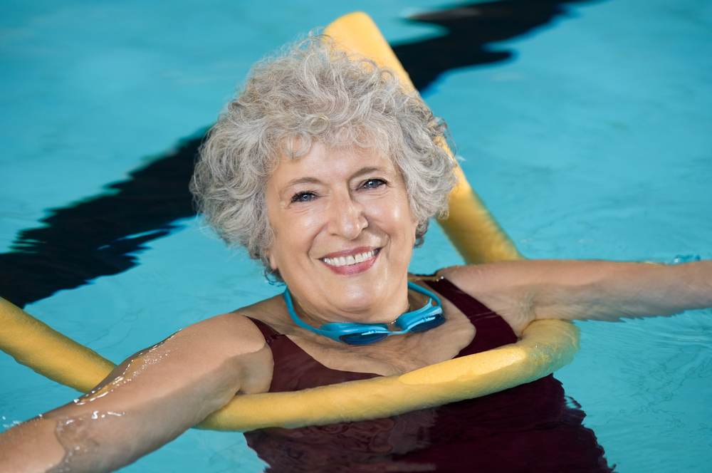 Senior woman in pool therapy floating on a pool noodle