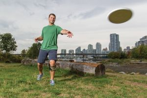 man throwing frisbee in knee brace