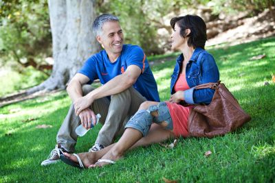 couple sitting on the grass with her in ossur unloader one knee brace